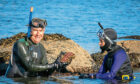 Keith Broomfield shows Gayle Ritchie a rock covered with pink encrusting corraline algae when the pair go snorkelling. Picture: Steven Brown.