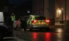 Police on a dark street responding to reports of an unexploded device