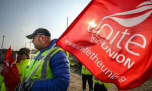 A Unite union member holding a red flag during a protest
