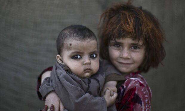 Afghan refugee girl, Khalzarin Zirgul, 6, holds her cousin, Zaman, 3 months, as they pose for a picture, while playing with other children in a slum on the outskirts of Islamabad, Pakistan