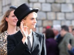 Cara Delevingne wears bold top hat and tails to the royal wedding (Gareth Fuller/PA)