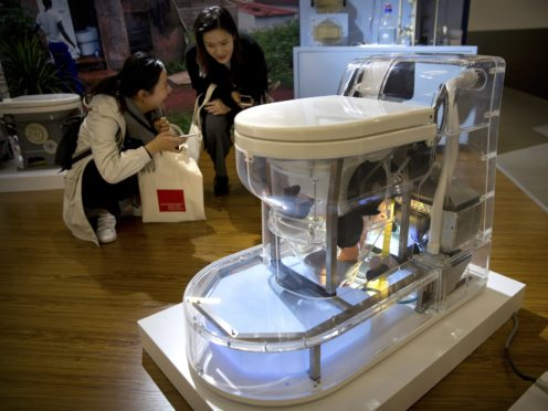 Visitors look at a model of a self-contained toilet at the Reinvented Toilet Expo in Beijing (Mark Schiefelbein/AP)