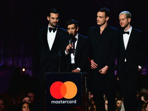 Matt Healy (centre) of the The 1975 accepts a Brit award (PA)