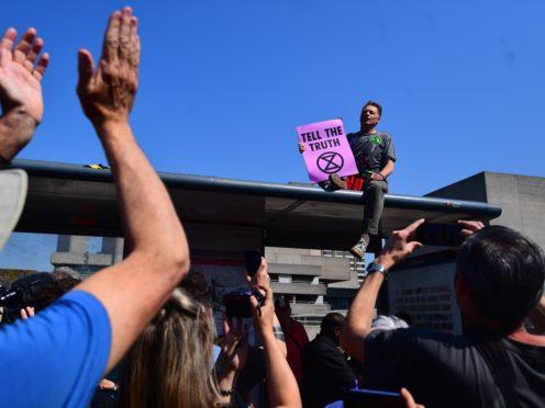 Chris Packham makes a speech on top of a bus shelter (Victoria Jones/PA)