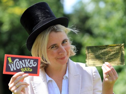 Auctioneer Catherine Southon holds the Golden Ticket and Wonka Bar props from the 1971 film Willy Wonka & The Chocolate Factory, which are going under the hammer (Gareth Fuller/PA)