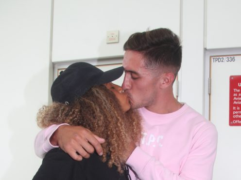 Amber Gill and Greg O'Shea share a kiss after arriving back in the UK (Yui Mok/PA)