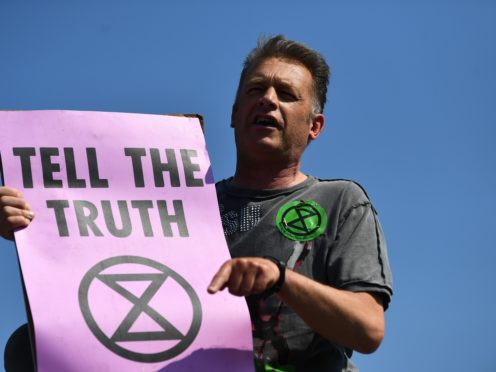 Chris Packham makes a speech on top of a bus stop during an Extinction Rebellion demonstration. (Victoria Jones/PA)