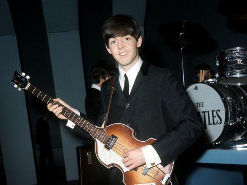 Sir Paul McCartney poses with one of his Hofner bass guitars (PA)