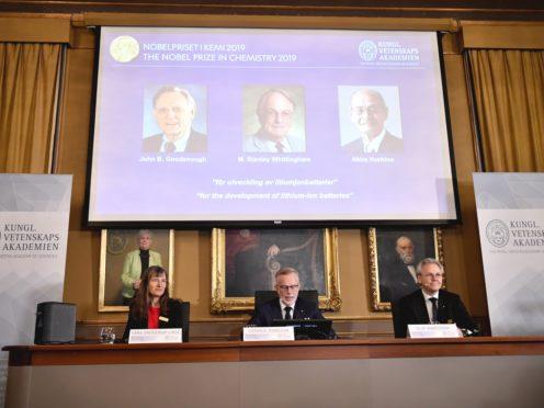 The winners of the 2019 Nobel Prize in Chemistry, shown on the screen, from left, John B Goodenough, M Stanley Whittingham, and Akira Yoshino (Naina Helen Jama/TT via AP)