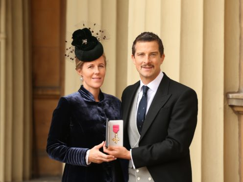 Bear Grylls and his wife Shara holding his OBE (Jonathan Brady/PA)