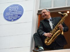Alex Garnett posing with Ronnie Scott?'s tenor saxophone at the site of his newly unveiled English Heritage Blue Plaque (English Heritage/Jed Leicester/PinPep/PA)