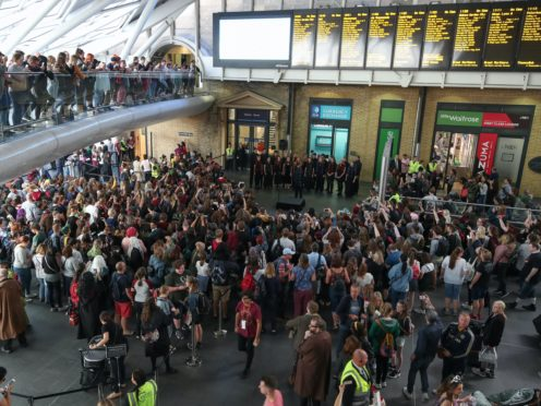 Harry Potter fans gather to watch as the Hogwarts Express appears on the departure board at London King's Cross (Chris Radburn/PA)