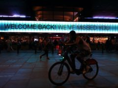 A cyclist rides past a sign saying 'Welcome Back! We've Missed You' displayed above the front of the BFI Southbank cinema in London (Yui Mok/PA)