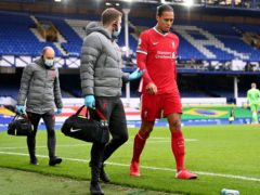 Virgil Van Dijk, right, leaves the game injured against Everton (Laurence Griffiths/PA)