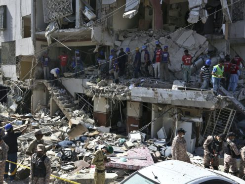Troops and rescue workers look for survivors amid the rubble of a damaged building following the explosion in Karachi, Pakistan (Fareed Khan/AP)
