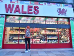 A shop owner pulls the shutters down on the Wales souvenir shop in Cardiff city centre (Ben Birchall/PA)