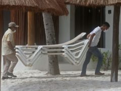 Beach hotel workers store chairs inside (AP)