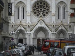 French policemen and forensic officers stand in front of Notre Dame church (Daniel Cole/AP)