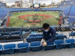 Atsuhiro Tanabe, a part-time stadium crew member, wipes seats of a baseball stadium, home for the Yokohama DeNA BayStars, seen during a media tour in Yokohama, south of Tokyo on Friday, Oct. 30, 2020. The tour was held to introduce device installed at the stadium to record behaviors of baseball audience members during a game for coronavirus control. (AP Photo/Hiro Komae)