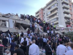 Rescue workers and local people try to reach residents trapped in the debris of a collapsed building, in Izmir, Turkey, Friday, Oct. 30, 2020, after a strong earthquake in the Aegean Sea has shaken Turkey and Greece. Turkey's Disaster and Emergency Management Presidency said Friday's earthquake was centered in the Aegean at a depth of 16,5 kilometers (10.3 miles) and registered at a 6.6 magnitude.(AP Photo/Ismail Gokmen)