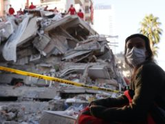 A local resident, staying outdoors for fear of aftershocks, watches as members of rescue services search for survivors in the debris of a collapsed building in Izmir, Turkey, Saturday, Oct. 31, 2020. Rescue teams on Saturday ploughed through concrete blocs and debris of eight collapsed buildings in Turkey's third largest city in search of survivors of a powerful earthquake that struck Turkey's Aegean coast and north of the Greek island of Samos, killing dozens Hundreds of others were injured (Darko Bandic/AP)
