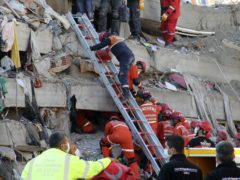 Rescue workers try to save residents trapped in the debris of a collapsed building, in Izmir (Ismail Gokmen/AP)