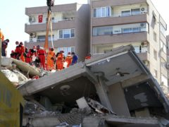Rescue workers try to save residents trapped in debris of a collapsed building, in Izmir (Ismail Gokmen/AP)