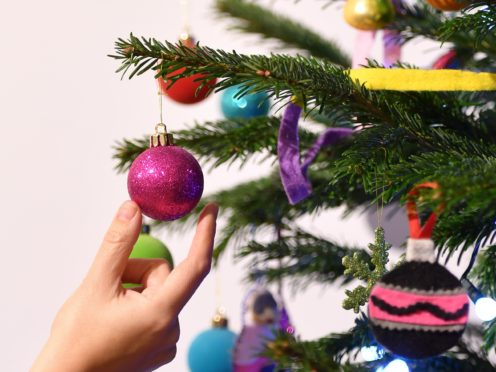 A woman adjusts a decoration on a Christmas tree (Dominic Lipinski/PA)
