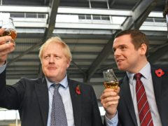 Douglas Ross, right, was repeatedly asked about comments made by Boris Johnson, left, about devolution (PA)