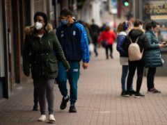 Shoppers wearing protective face masks walk along High Street, Dudley, in the West Midlands in mid-October Ethnic minorities, people with disabilities, renters and young adults are at particular risk of problem debts this winter, the IPPR said (PA)