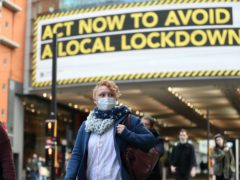 A woman wearing a face mask walks through Manchester. Greater Manchester will be placed under stricter coronavirus controls after last-ditch talks with the Prime Minister aimed at securing additional financial support concluded without an agreement (Martin Rickett/PA)