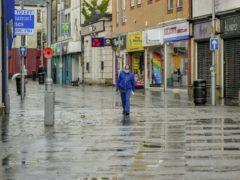 A lone man walks through the shopping centre of Bridgend (Ben Birchall/PA)