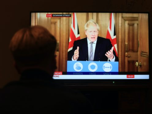 A member of the public watches Boris Johnson announcing a new England-wide lockdown (Mike Egerton/PA)