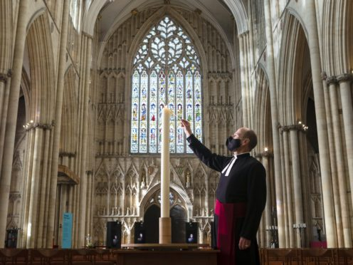 Canon Michael Smith lights a candle during York Minster's Season of Remembrance (Danny Lawson/PA)
