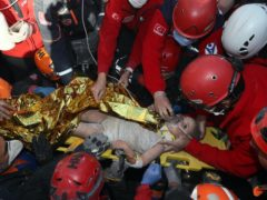 In this photo provided by the government's Search and Rescue agency AFAD, rescue workers, who were trying to reach survivors in the rubble of a collapsed building, surround Ayda Gezgin in the Turkish coastal city of Izmir, Turkey, Tuesday, Nov. 3, 2020, after they have pulled the young girl out alive from the rubble of a collapsed apartment building four days after a strong earthquake hit Turkey and Greece. The girl, Ayda Gezgin, was being taken into an ambulance on Tuesday, wrapped in a thermal blanket, amid the sound of cheers and applause from rescue workers. (AFAD via AP)