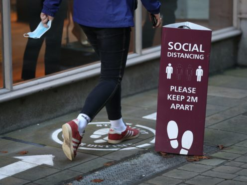 A person walks past a social distancing sign near the High Street in Winchester (PA)