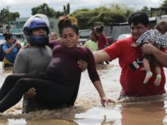 A pregnant woman is carried out of an area flooded by water brought by Hurricane Eta in Planeta, Honduras (Delmer Martinez/AP)