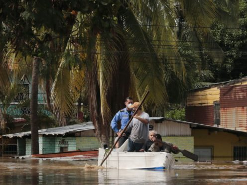 Residents paddle a boat through a flooded street in the aftermath of Hurricane Eta in Honduras (AP)