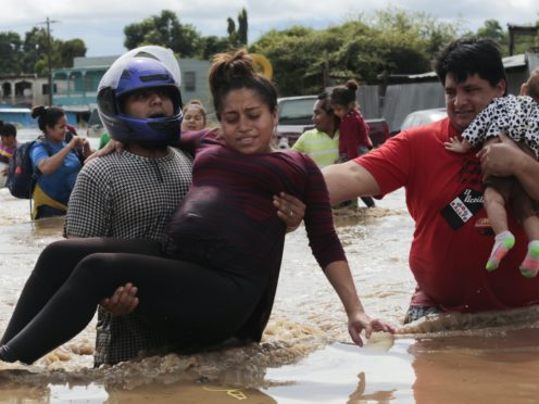 A pregnant woman is carried out of an area flooded by water brought by Hurricane Eta. Hurricane Iota is set to hit the same area just a week later (Delmer Martinez/AP)