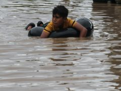 A child floats in a flooded street in the aftermath of Hurricane Eta, in Planeta, Honduras (AP)