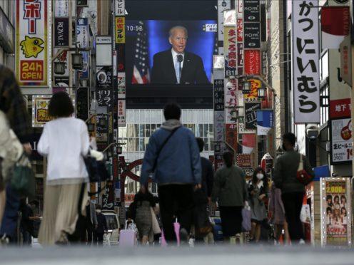A screen in Shinjuku shopping district in Tokyo shows a broadcast of president-elect Joe Biden speaking on Sunday (Kiichiro Sato/AP)