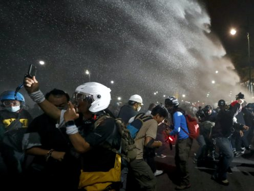Police use water cannons to disperse pro-democracy protesters during a street march in Bangkok (Sakchai Lalit/AP)