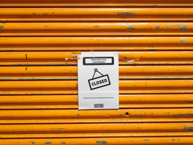 A closed sign outside a shuttered shop unit in Brixton (PA)