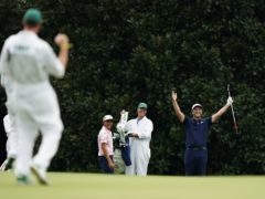 Rickie Fowler, left, watches as Jon Rahm, celebrates chipping into the hole on the 16th green (Matt Slocum/AP)