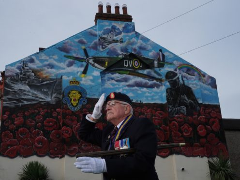 Eric Howden, 76, salutes in front of a commemorative war mural in Redcar (Owen Humphreys/PA)