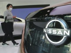 A visitor walks past a car at Nissan showroom in Tokyo (Koji Sasahara/AP)
