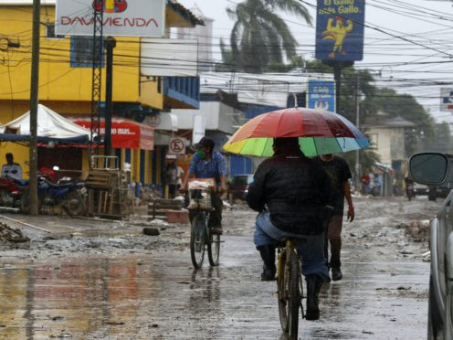 Locals move on street barely cleared from the debris of the last storm, before Hurricane Iota makes landfall in La Lima, Honduras (Delmer Martinez/AP)