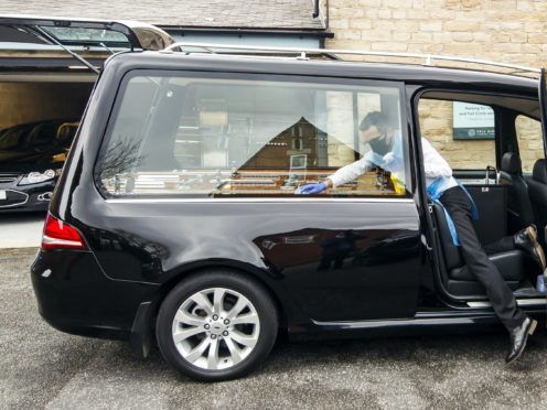 Funeral director Andrew Atkins wears PPE as he disinfects a hearse at Full Circle Funerals in Bramley, Leeds (Danny Lawson/PA)