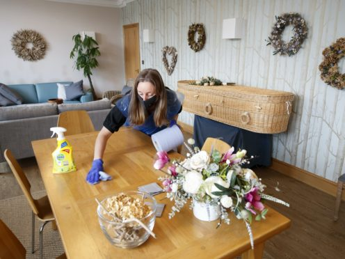 Funeral director Sarah Jones wears PPE as she disinfects at Full Circle Funerals (Danny Lawson/PA)