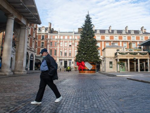 A man wearing a face mask passes the Christmas tree in Covent Garden Piazza, London, as England continues a four week national lockdown to curb the spread of coronavirus.